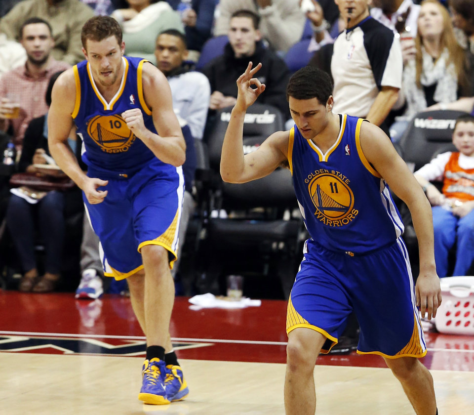 Photo - Golden State Warriors guard Klay Thompson (11) celebrates his three-point shot with forward David Lee (10) nearby, in the second half of an NBA basketball game against the Washington Wizards, Sunday, Jan. 5, 2014, in Washington. Thompson had 26 points, Lee had 21 points, and the Warriors won 112-96. (AP Photo/Alex Brandon)