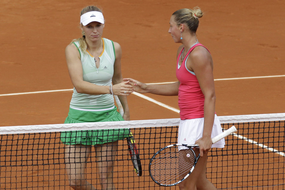Photo - Denmark's Caroline Wozniacki, left, shakes hands with Belgium's Yanina Wickmayer after losing the first round match of the French Open tennis tournament at the Roland Garros stadium, in Paris, France, Tuesday, May 27, 2014. (AP Photo/Darko Vojinovic)