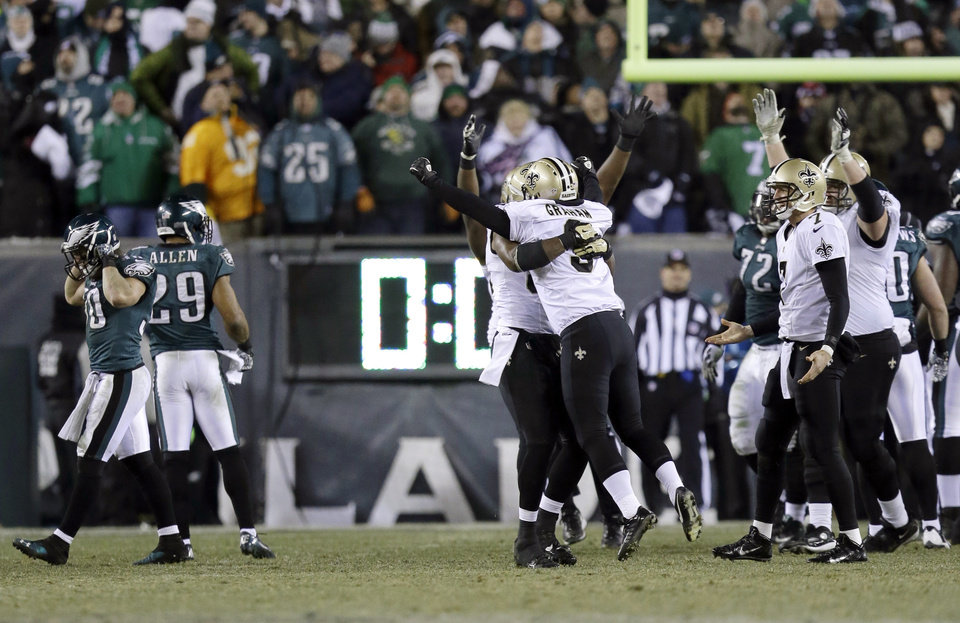 Photo - New Orleans Saints' Shayne Graham celebrates after kicking the game-winning field goal during the second half of an NFL wild-card playoff football game against the Philadelphia Eagles, Saturday, Jan. 4, 2014, in Philadelphia. The Saints won 26-24.  (AP Photo/Julio Cortez)