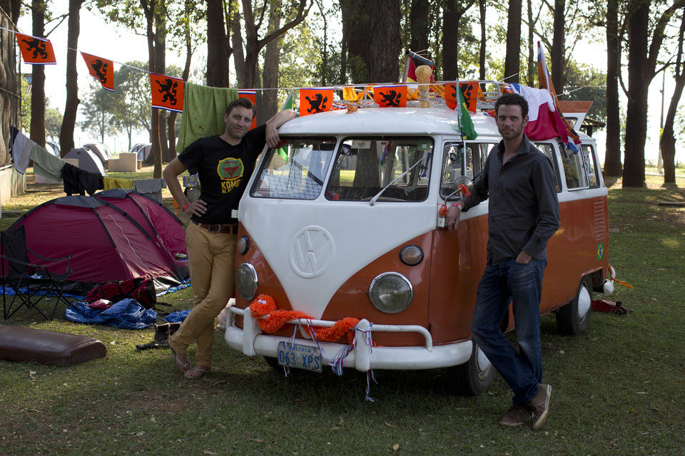 Photo - Laurens Kraal, left and Udo Van Heteren stand next to their Kombi van after driving from Bolivia to Brazil at the Oranjecamping site during the 2014 soccer World Cup in Sao Paulo, Brazil, Sunday, June 22, 2014. The group of seven Dutch men arrived at Sao Paulo after a 13-day journey from Bolivia in the orange hippie van that dates back to at least 45 years. (AP Photo/Dario Lopez-Mills)