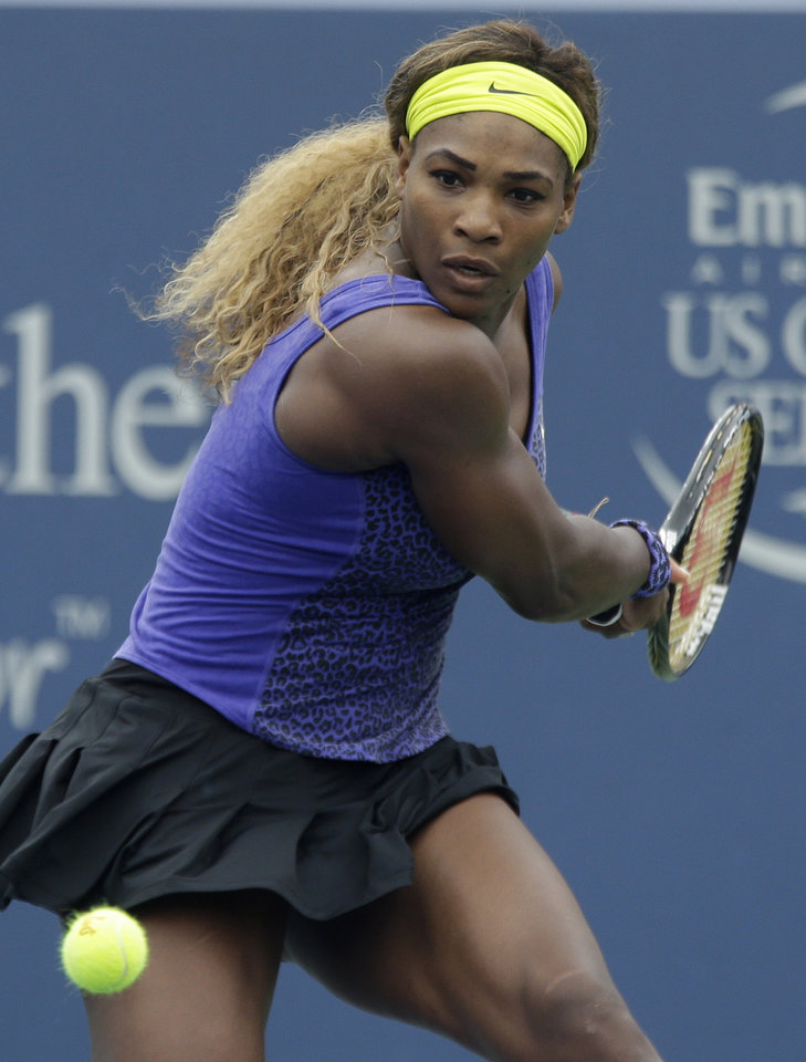 Photo - Serena Williams eyes a backhand against Ana Ivanovic, from Serbia, during a final match at the Western & Southern Open tennis tournament, Sunday, Aug. 17, 2014, in Mason, Ohio. (AP Photo/Al Behrman)