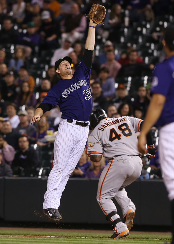 Photo - Colorado Rockies first baseman Justin Morneau, left, fields the throw as San Francisco Giants' Pablo Sandoval reaches first base on an infield single in the fourth inning of a baseball game in Denver on Monday, April 21, 2014. (AP Photo/David Zalubowski)