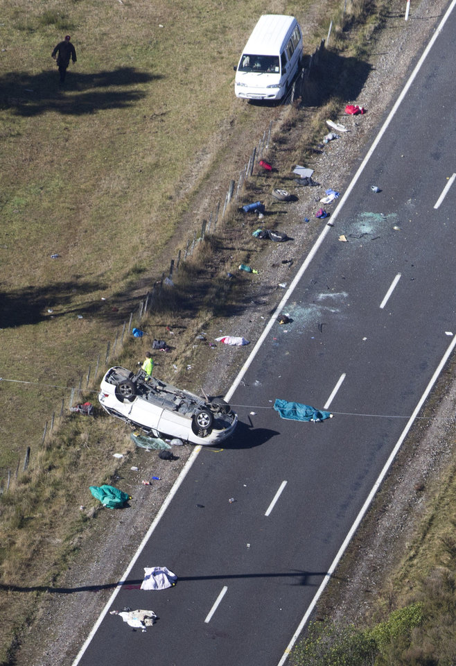 Photo -   Police and fire crew examine the scene of a minivan crash near Turangi, New Zealand, Saturday, May 12, 2012. Three Boston University students who were studying in New Zealand were killed Saturday when their minivan crashed. At least five other students from the university were injured in the accident, including one who was in critical condition. (AP Photo/New Zealand Herald, John Cowpland) NEW ZEALAND OUT, AUSTRALIA OUT