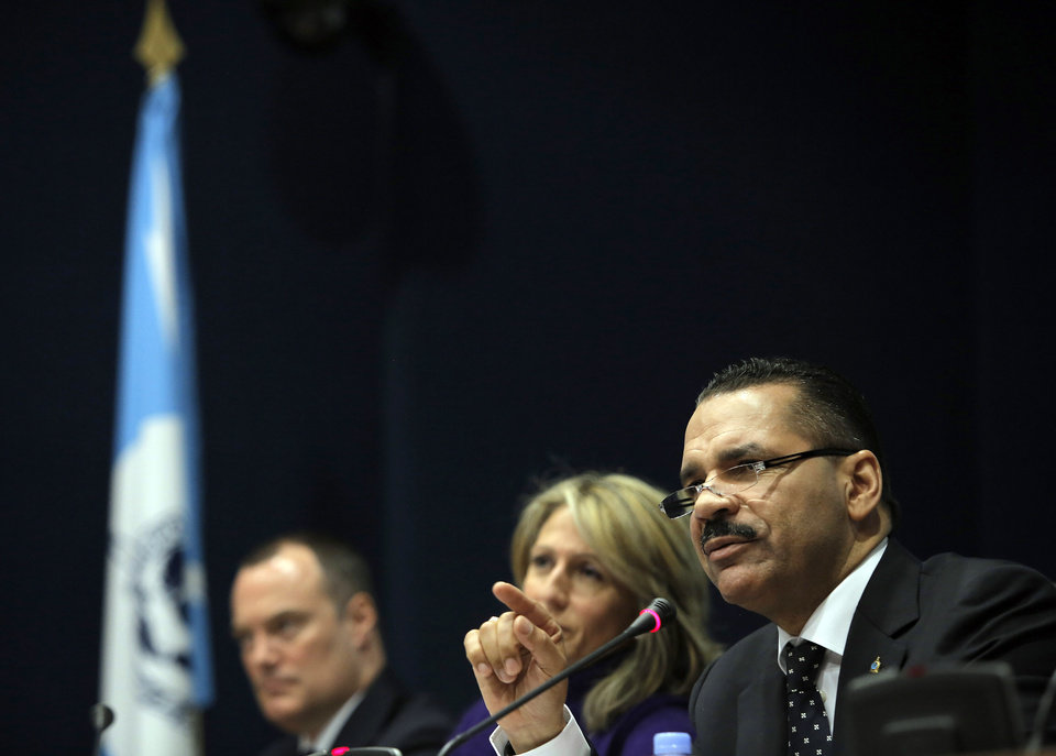 Photo - Interpol Secretary General, Ronald K. Noble, makes a point during a presser held at the Interpol headquarters in Lyon, central France, Tuesday, March 11, 2014.  Interpol has released an image of two Iranians who were traveling with stolen passports on a missing Malaysia Airlines jetliner. Noble said Tuesday the two men traveled to Malaysia on their Iranian passports, then apparently switched to the stolen Austrian and Italian documents.  Seated far left : Michael O'Connell, director of operational police support, and center Roraima Andriani, Interpol chief of staff. (AP Photo/Laurent Cipriani)