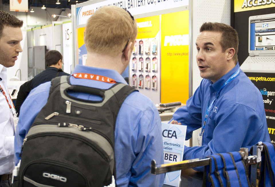 Photo - Dustin Holt talks to potential buyers Wednesday at the 2013 international consumer electronics show in Las Vegas.  Photos by PAUL RIEDL, For The Oklahoman