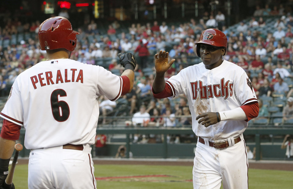 Photo - Arizona Diamondbacks' Didi Gregorius, right, gets a high-five from teammate David Peralta (6) after Gregorius scored a run against the Milwaukee Brewers during the first inning of a baseball game on Tuesday, June 17, 2014, in Phoenix. (AP Photo/Ross D. Franklin)