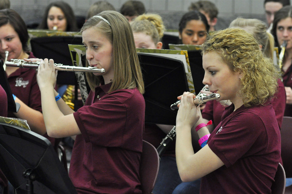 Photo -    Jailynn Grubbs, left, 17, and Melissa Reed, 16, play in the Symphonic Band during the Swine Week concert at Edmond Memorial High School on Thursday. Photo by M. Tim Blake, for The Oklahoman   M. Tim Blake