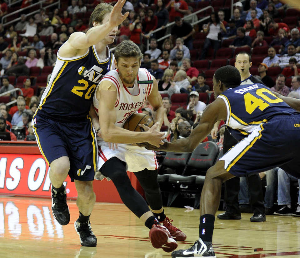 Houston Rockets' Chandler Parsons, center, drives between Utah Jazz defenders Gordon Hayward (20) and Jeremy Evans (40) in the first half of an NBA basketball game on Saturday, Dec. 1, 2012, in Houston. (AP Photo/Pat Sullivan)