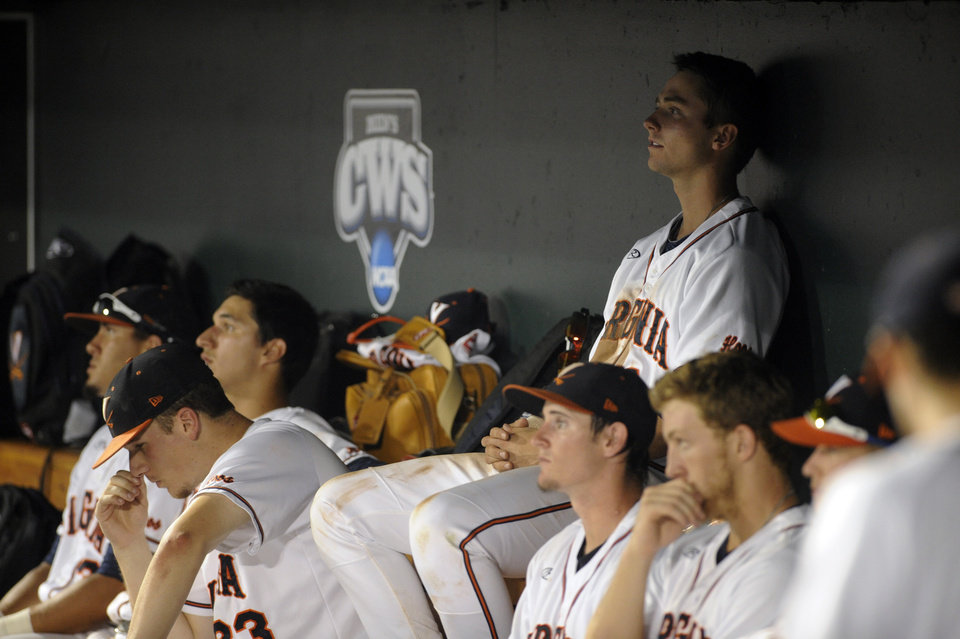 Photo - Virginia players sit in the dugout after a 3-2 loss to Vanderbilt in the deciding game of the best-of-three NCAA baseball College World Series finals in Omaha, Neb., Wednesday, June 25, 2014. (AP Photo/Eric Francis)