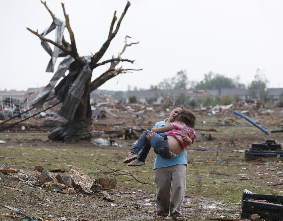 Photo - A woman carries her child through a field near the collapsed Plaza Towers Elementary School in Moore, Okla., Monday, May 20, 2013. A tornado as much as a mile (1.6 kilometers) wide with winds up to 200 mph (320 kph) roared through the Oklahoma City suburbs Monday, flattening entire neighborhoods, setting buildings on fire and landing a direct blow on an elementary school. (AP Photo Sue Ogrocki)
