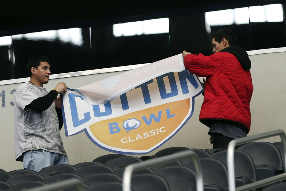 Photo - Workers prepare the stands during media day for the Cotton Bowl NCAA college football game at Cowboys Stadium, Sunday, Dec. 30, 2012, in Arlington, Texas. Oklahoma and Texas A&M are scheduled to play each other on Jan. 4, 2013. (AP Photo/LM Otero) ORG XMIT: TXMO109
