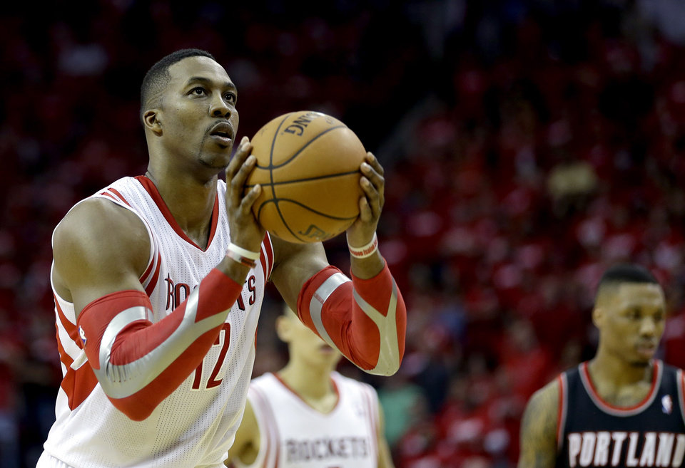 Photo - Houston Rockets' Dwight Howard (12) shoots a free throw against the Portland Trail Blazers during overtime in Game 1 of an opening-round NBA basketball playoff series Sunday, April 20, 2014, in Houston. The Trail Blazers won 122-120 in overtime. Howard was 9-for-17 in free throws. (AP Photo/David J. Phillip)