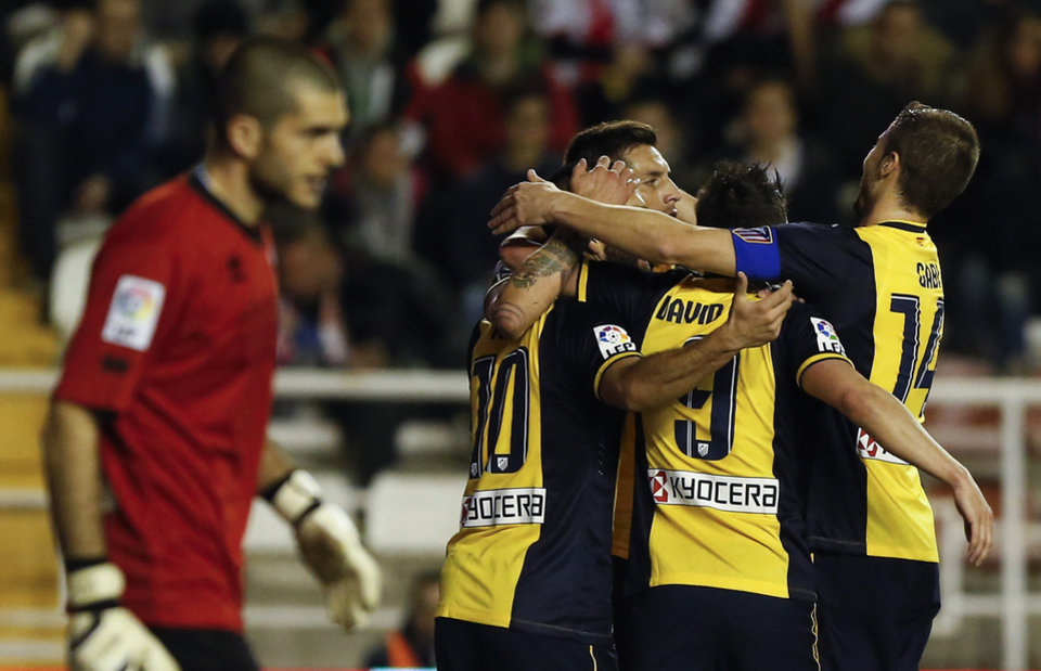 Photo - Atletico's Arda Turan, center left, celebrates his goal with teammates during the Spanish La Liga soccer match between Rayo Vallecano and Atletico de Madrid at the Vallecas stadium in Madrid, Spain, Sunday, Jan. 26, 2014. (AP Photo/Andres Kudacki)