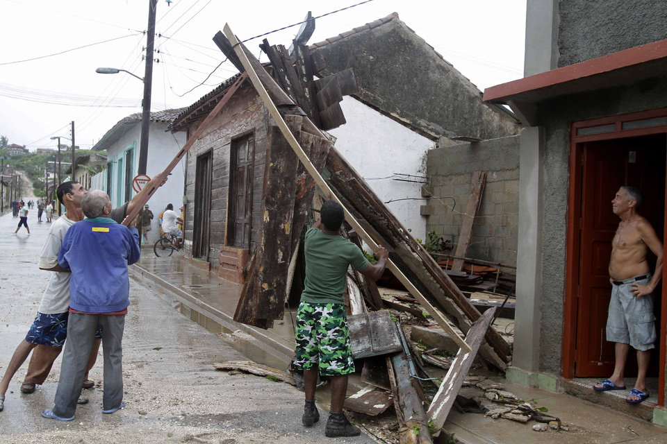 Photo -   Men try to free an electrical wire wire from debris, which was turned off last night, after the passing of Hurricane Sandy in Gibara, Cuba, Thursday, Oct. 25, 2012. Hurricane Sandy blasted across eastern Cuba on Thursday as a potent Category 2 storm and headed for the Bahamas after causing at least two deaths in the Caribbean. (AP Photo/Franklin Reyes)