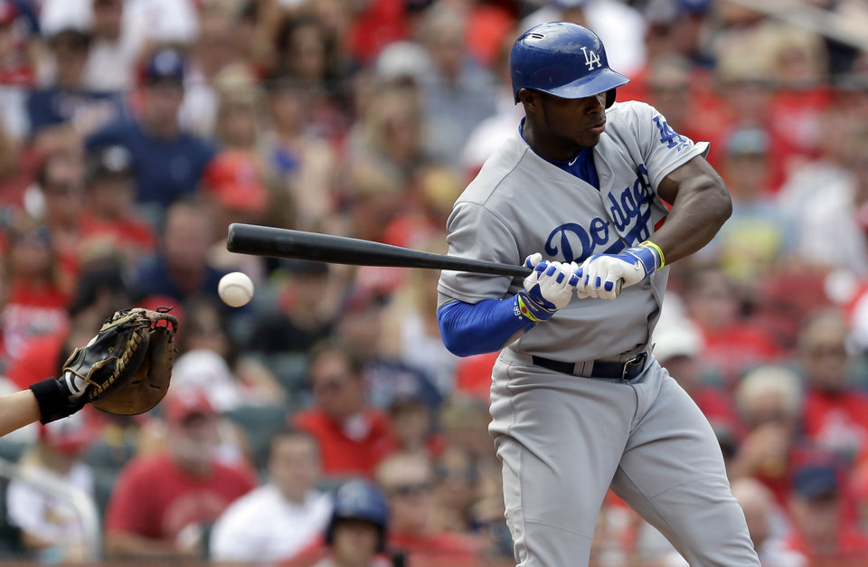 Photo - A ball bounces off the left hand of Los Angeles Dodgers' Yasiel Puig during the third inning of a baseball game against the St. Louis Cardinals Saturday, July 19, 2014, in St. Louis. Puig left the game in the eighth inning and the Cardinals went on to win 4-2. (AP Photo/Jeff Roberson)