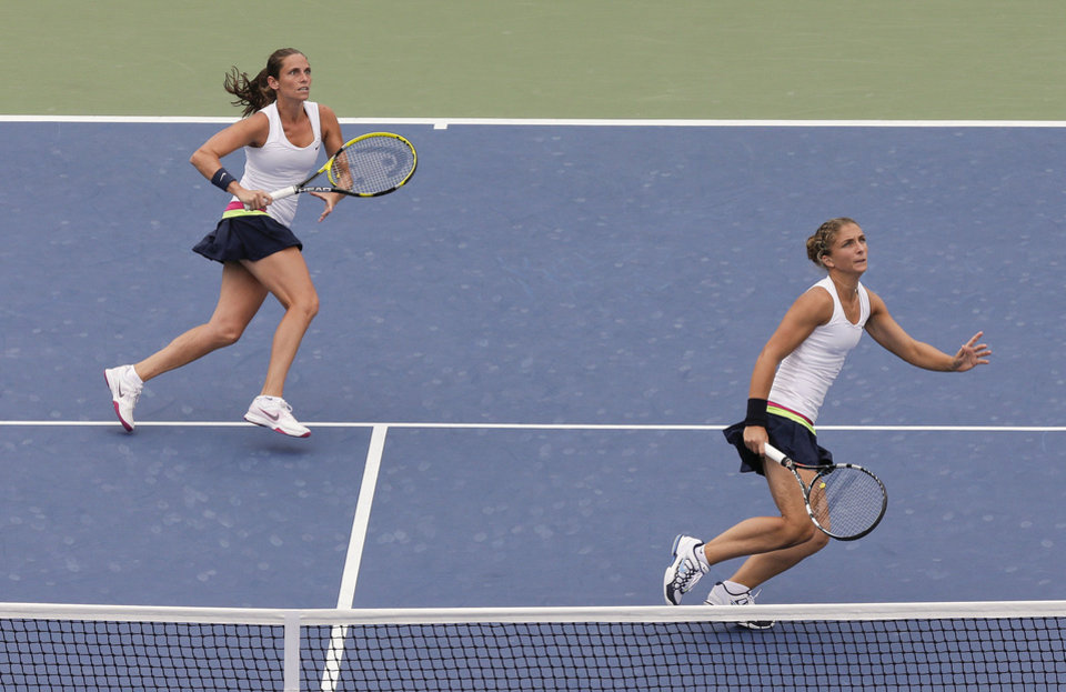 Photo -   Italy's Roberta Vinci, left, and Sara Errani chase after a lob shot while playing Nuria Llagostera Vives and Maria Jose Martinez Sanchez during the women's doubles semifinals of the 2012 US Open tennis tournament, Thursday, Sept. 6, 2012, in New York. (AP Photo/Julie Jacobson)
