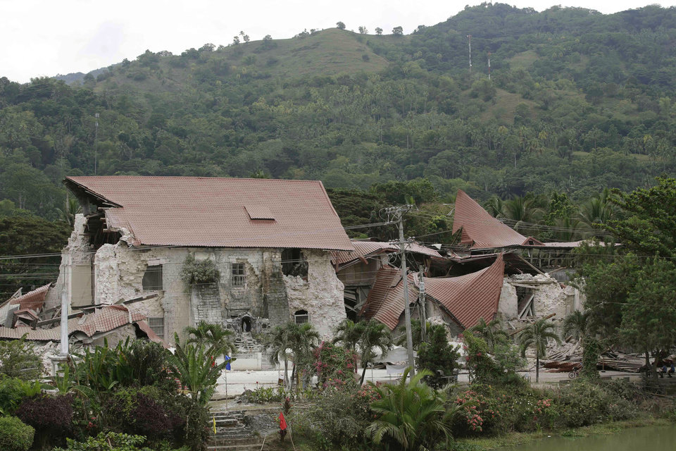 Photo - Debris lies near the damaged Saint Peter church in Loboc township, Bohol province in central Philippines Wednesday, Oct. 16, 2013, a day after a 7.2-magnitude quake hit Bohol and Cebu provinces. The tremor collapsed buildings and cracked roads Tuesday morning, causing multiple deaths across the central region.  (AP Photo/Bullit Marquez)