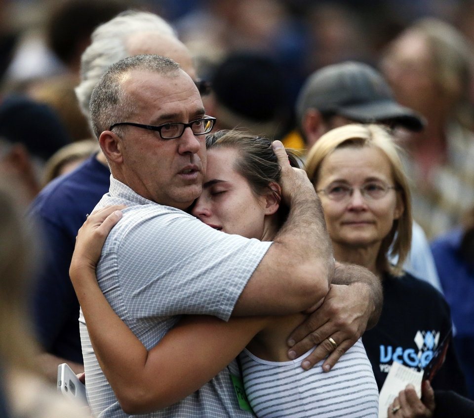 Photo - Family members hug during a community vigil on Tuesday, July 2, 2013.  in Prescott, Ariz. for the 19 firefighters from Granite Mountain Interagency Hotshot Crew that were killed battling a wildfire near Yarnell, Ariz. The elite crew of firefighters were overtaken by the out-of-control blaze as they tried to protect themselves from the flames under fire-resistant shields on Sunday. (AP Photo/Chris Carlson)