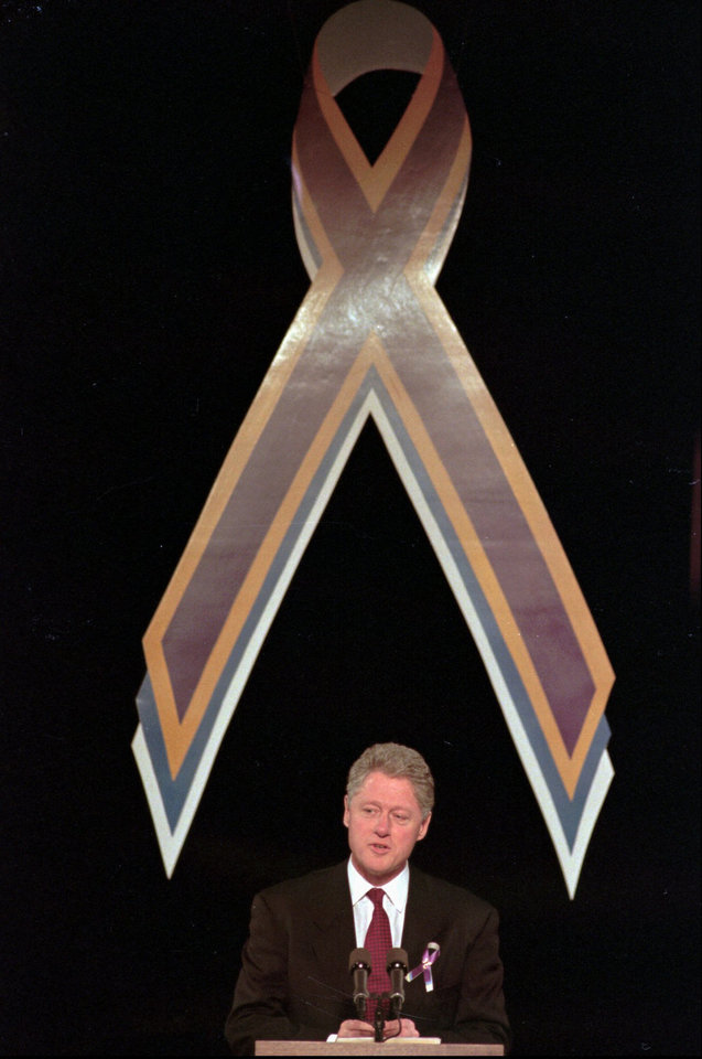 Photo - President Clinton speaks on Friday, April 5, 1996, in Oklahoma City to family members and survivors of the terrorist car bombing of the Alfred P. Murrah Federal Building on April 19, 1995. A large ribbon that has become the symbol of the survivors hangs over his head. (AP Photo/J. Pat Carter)