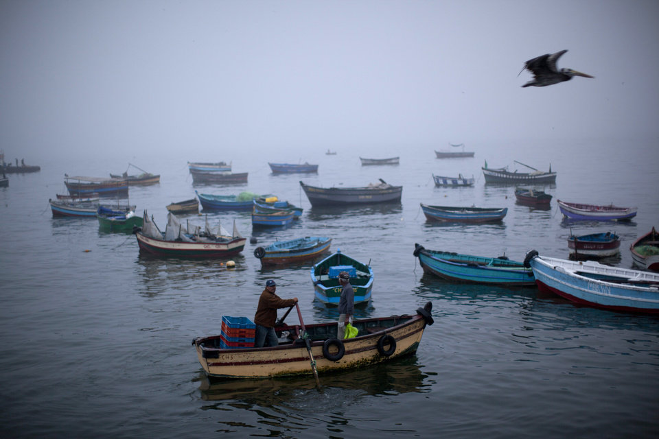 Photo - Fishermen navigate their boat out of the Chorrillo dock in the Pacific Ocean waters of Lima, Peru, Wednesday, April 2, 2014. Chilean authorities discovered surprisingly light damage Wednesday from a magnitude-8.2 quake that struck in the Pacific Ocean, Tuesday evening, near the mining port of Iquique, about 87 miles from the Peruvian border. Tsunami warnings issued for Chile, Peru and Ecuador have been lifted. Six deaths have been reported. (AP Photo/Rodrigo Abd) (AP Photo/Rodrigo Abd)