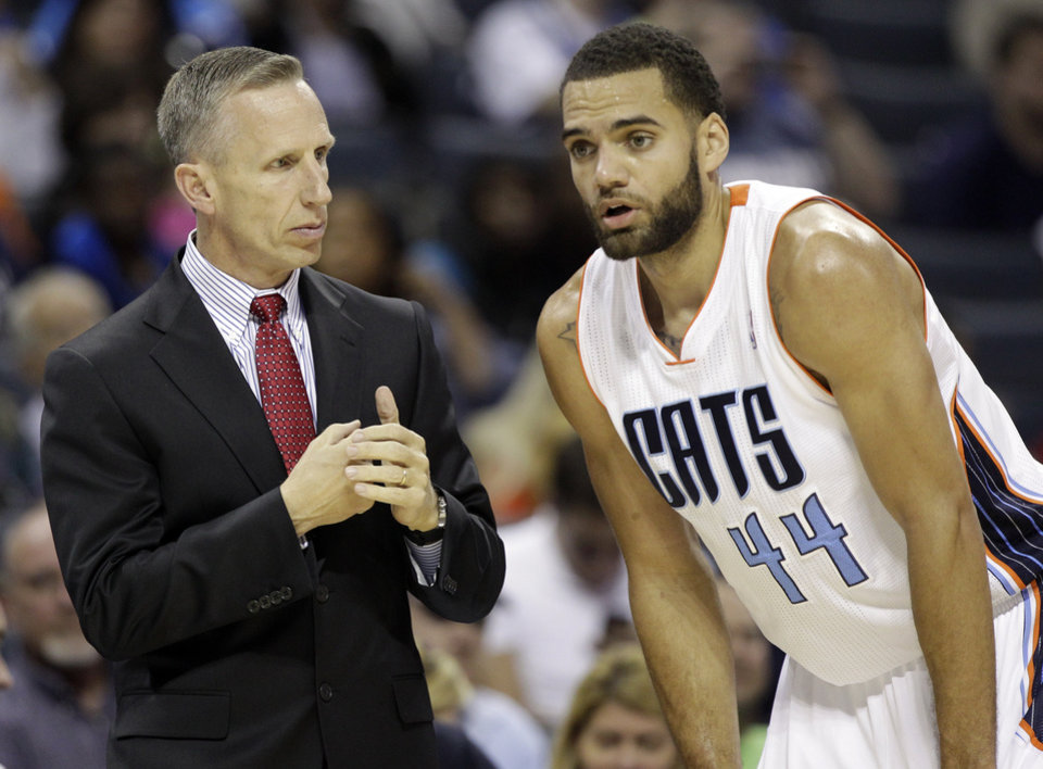 Charlotte Bobcats coach Mike Dunlap, left, talks with Jeffery Taylor, right, during the first half of an NBA basketball game against the Dallas Mavericks in Charlotte, N.C., Saturday, Nov. 10, 2012. (AP Photo/Chuck Burton)