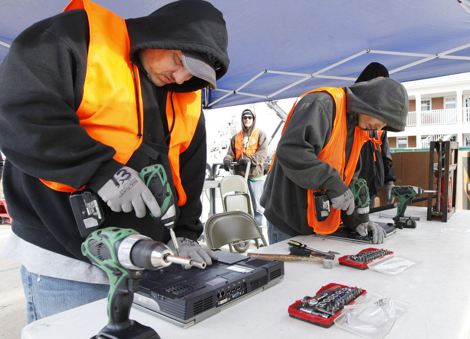 Photo - Jamie Morris, left, and Cody Hamby, with CDR Global, destroy potentially sensitive computer equipment during Edmond's annual Operation Clean Streets.