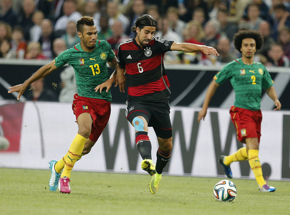 Photo - Germany's Sami Khedira, right, and Cameroon's Eric M. Choupo-Moting challenge for the ball during a soccer friendly match between Germany and Cameroon in Moenchengladbach, Germany, Sunday, June 1, 2014. (AP Photo/Michael Probst)