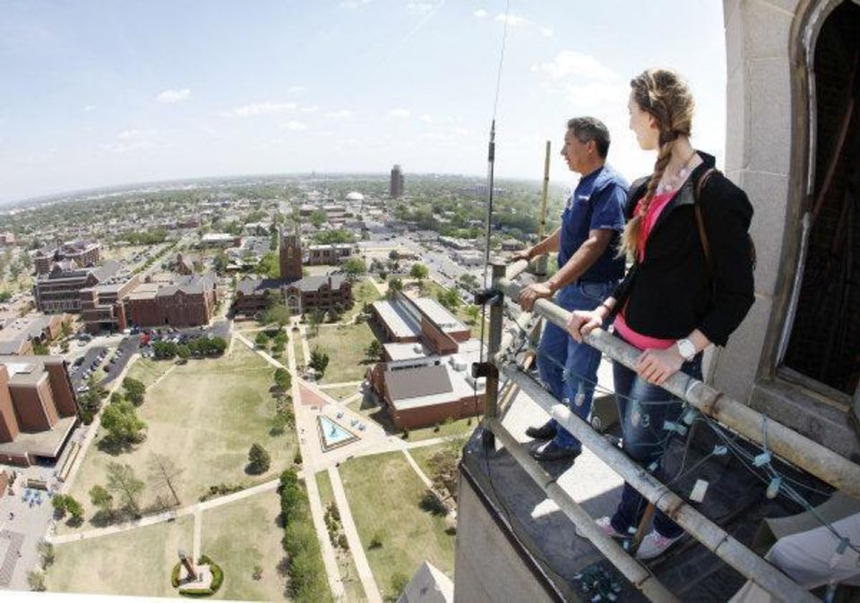 Photo - Oklahoman reporter Amanda Alfanos and facilities worker Victor Zuniga look out from the catwalk at the top of the 286 ft. tall GoldStar Memorial building on the campus of Oklahoma City University in Oklahoma City, OK, Thursday, April 14, 2011. By Paul Hellstern, The Oklahoman ORG XMIT: KOD  PAUL HELLSTERN
