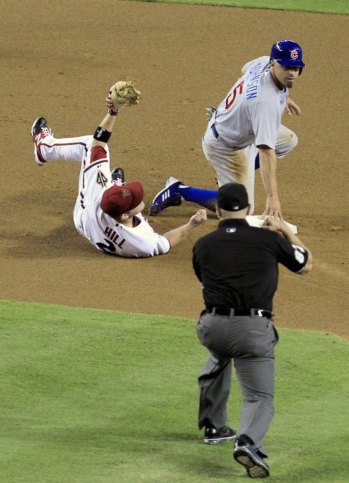 Photo -   Arizona Diamondbacks' Aaron Hill (2) holds on to the ball after tagging out Chicago Cubs' Reed Johnson (5) who was trying to steal second base as umpire Scott Barry makes the call during the first inning in a baseball game on Friday, June 22, 2012, in Phoenix.(AP Photo/Ross D. Franklin)