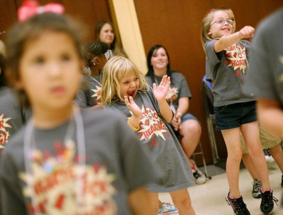 Photo - Sarah Johnson, center, and Jadyn Barefoot react as they learn dance steps during a class taught by two Thunder Girls at the Oklahoma City Museum of Art. The dance class was one of many activities of the weeklong Hearts for Hearing summer camp in downtown Oklahoma City this week. Photo by John Clanton, The Oklahoman  JOHN CLANTON