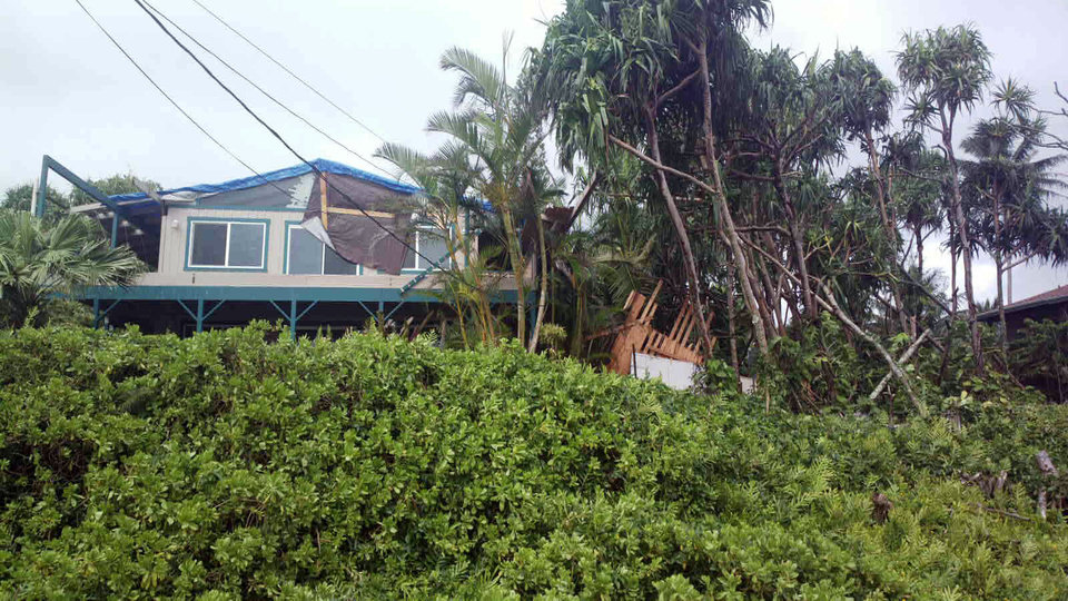 Photo - This photo provided by Andrew Fujimura shows the damage from Tropical Storm Iselle on a home in Puna, Hawaii, on Saturday, Aug. 9, 2014. Tropical Storm Iselle, knocked down trees, battered roofs and left the isolated area without electricity. (AP Photo/Courtesy Andrew Fujimura)