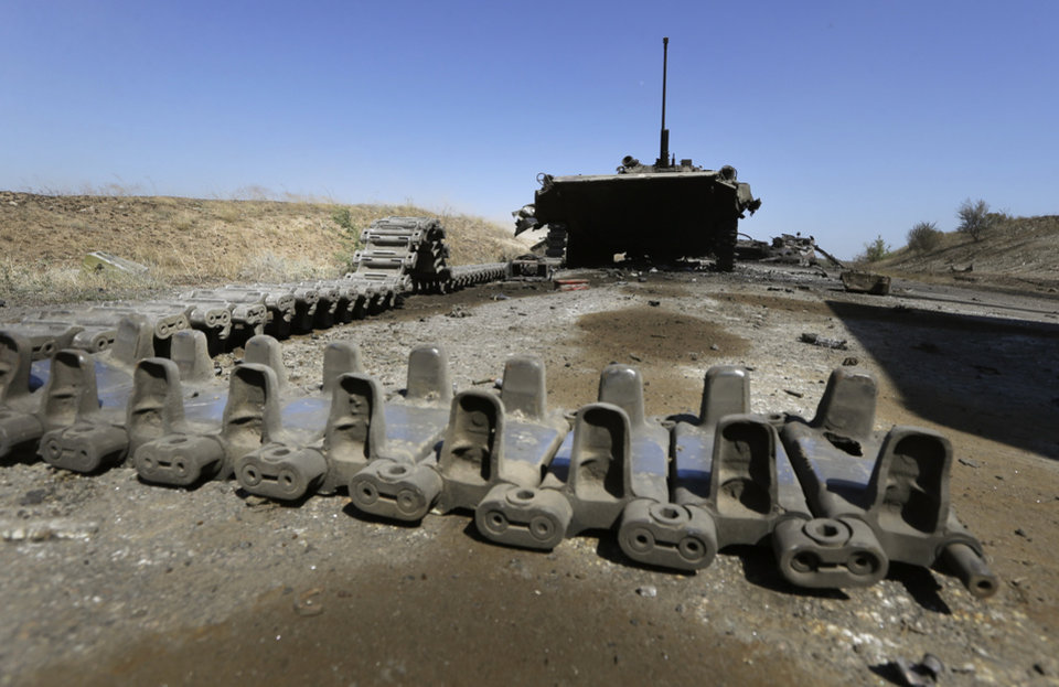 Photo - Remnants of a column of destroyed Ukrainian military vehicles are abandoned near the village of Novokaterynivka, eastern Ukraine, Tuesday, Sept. 2, 2014. Ukrainian troops have over the past week suffered a string of major military losses in their offensive against Russian-backed separatist rebels, losing large swathes of territory and having hundreds of soldiers captured. (AP Photo/Sergei Grits)