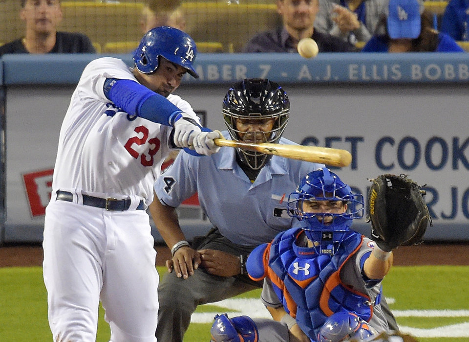 Photo - Los Angeles Dodgers' Adrian Gonzalez hits a hree-run home run in front of New York Mets catcher Travis d'Arnaud and home plate umpire CB Bucknor during the fifth inning of a baseball game, Saturday, Aug. 23, 2014, in Los Angeles.  (AP Photo/Mark J. Terrill)