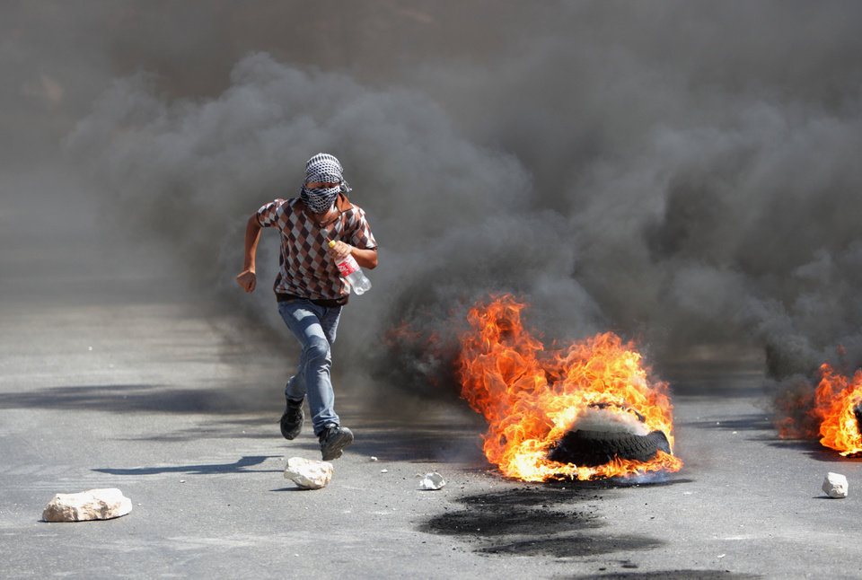 Photo - A Palestinian protester runs away from Israeli soldiers during clashes, following a protest against the Israeli military action in Gaza, in the West Bank city of Nablus on Friday, Aug. 22, 2014. (AP Photo/Nasser Ishtayeh)