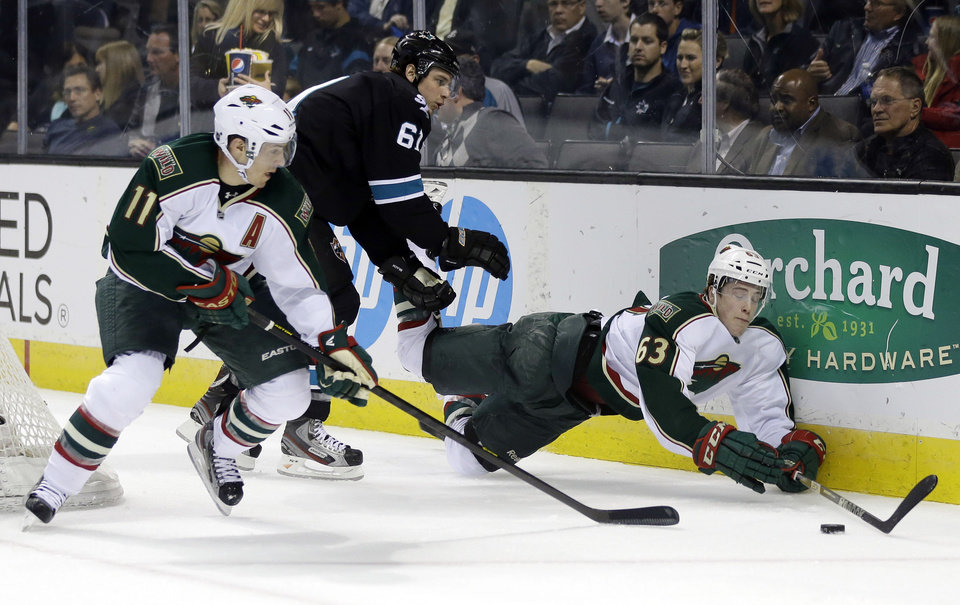 Minnesota Wild right wing Charlie Coyle, right, falls down against the boards next to San Jose Sharks defenseman Justin Braun (61) and Wild left wing Zach Parise (11) during the second period of an NHL hockey game in San Jose, Calif., Thursday, April 18, 2013. (AP Photo/Marcio Jose Sanchez)