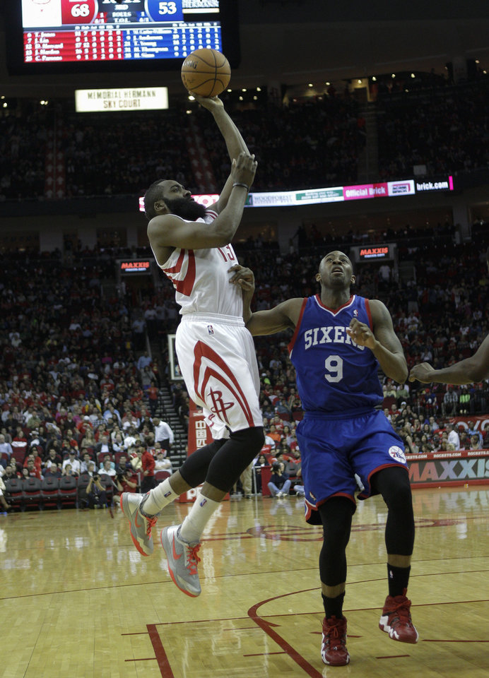 Photo - Houston Rockets' James Harden (13) shoots over Philadelphia 76ers' James Anderson (9) during the second half of an NBA basketball game on Thursday, March 27, 2014, in Houston. Houston won 120-98. (AP Photo/Bob Levey)