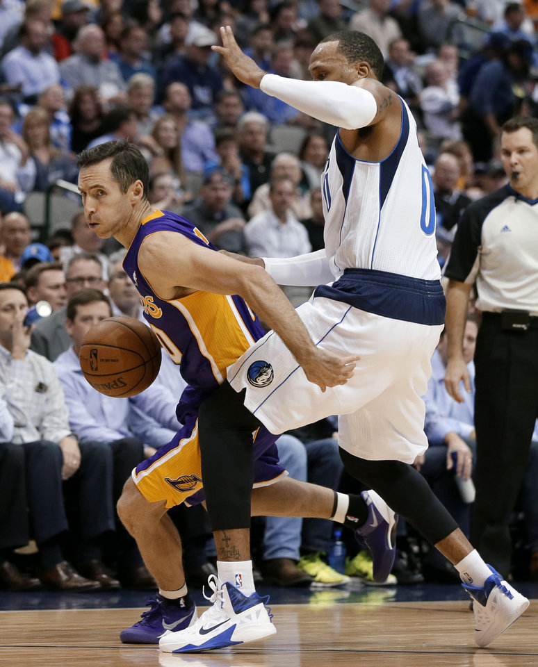 Photo - Los Angeles Lakers' Steve Nash (10) slips past the defense of Dallas Mavericks' Shawn Marion as Nash moves the ball up court in the first half of an NBA basketball game, Tuesday, Nov. 5, 2013, in Dallas. (AP Photo/Tony Gutierrez)