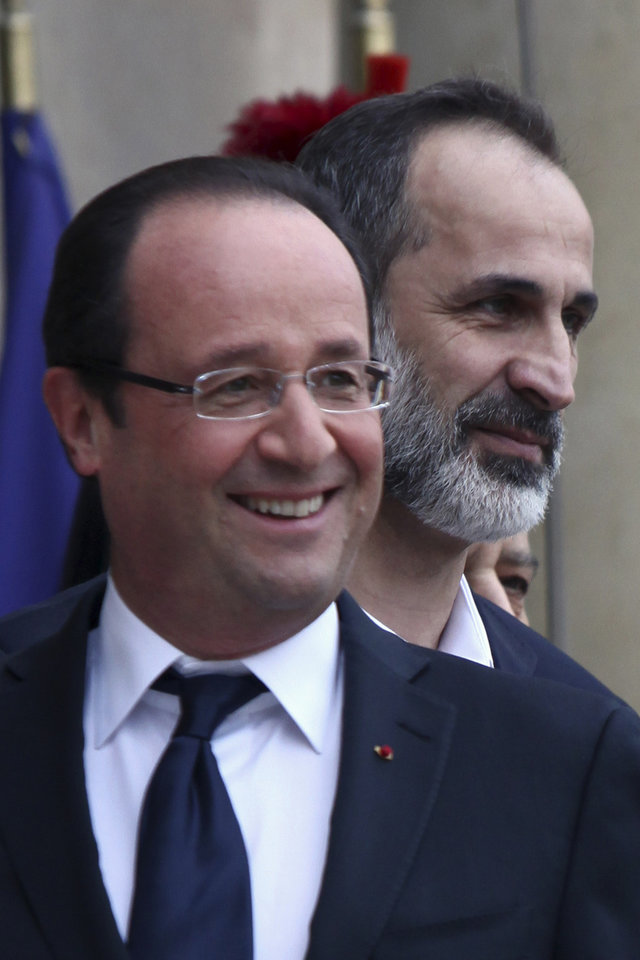 Photo -   French President Francois Hollande, left, smiles as he welcomes head of the new Syrian National Coalition for Opposition and Revolutionary Forces Mouaz al-Khatib, right, prior to a meeting, at the Elysee Palace, in Paris, Saturday, Nov. 17, 2012. France has taken a leading role among Western countries in supporting Syria's rebels. On Tuesday, it became the first Western nation to formally recognize Syria's newly formed opposition coalition as the sole legitimate representative of the Syrian people. (AP Photo/Thibault Camus)