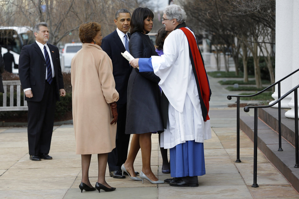 Photo - First lady Michelle Obama is greeted by Rev. Luis Leon at St. John's Church in Washington, Monday, Jan. 21, 2013, as the first family arrived for a church service during the 57th Presidential Inauguration. (AP Photo/Jacquelyn Martin)