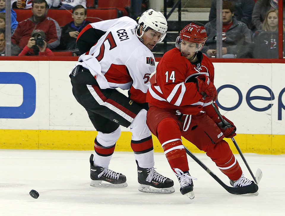 Photo - Carolina Hurricanes' Nathan Gerbe (14) over skates the puck while being defended by Ottawa Senators Codey Ceci (5) during the second period of an NHL hockey game in Raleigh, N.C., Saturday, Jan. 25, 2014. Hurricanes won 6-3. (AP Photo/Karl B DeBlaker)