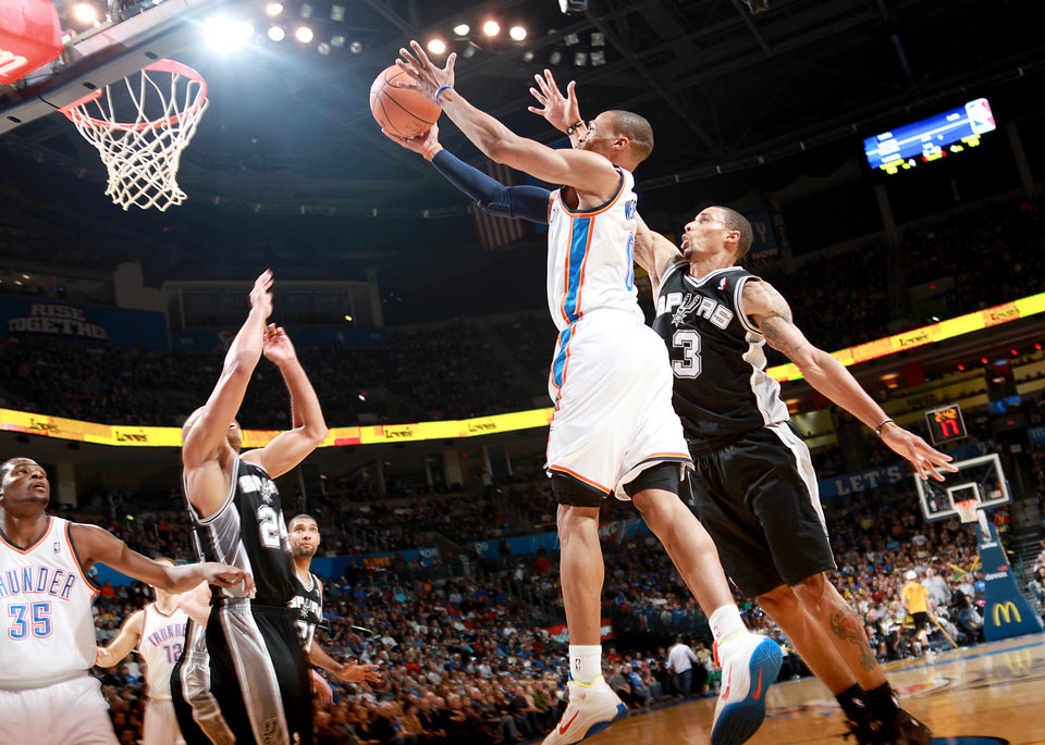 Photo - Oklahoma City's Russell Westbrook puts up a shot in front of San Antonio's George Hill and Richard Jefferson during their NBA basketball game in downtown Oklahoma City  on Sunday, Nov. 14, 2010. The Thunder lost to the Spurs 117-104. Photo by John Clanton, The Oklahoman