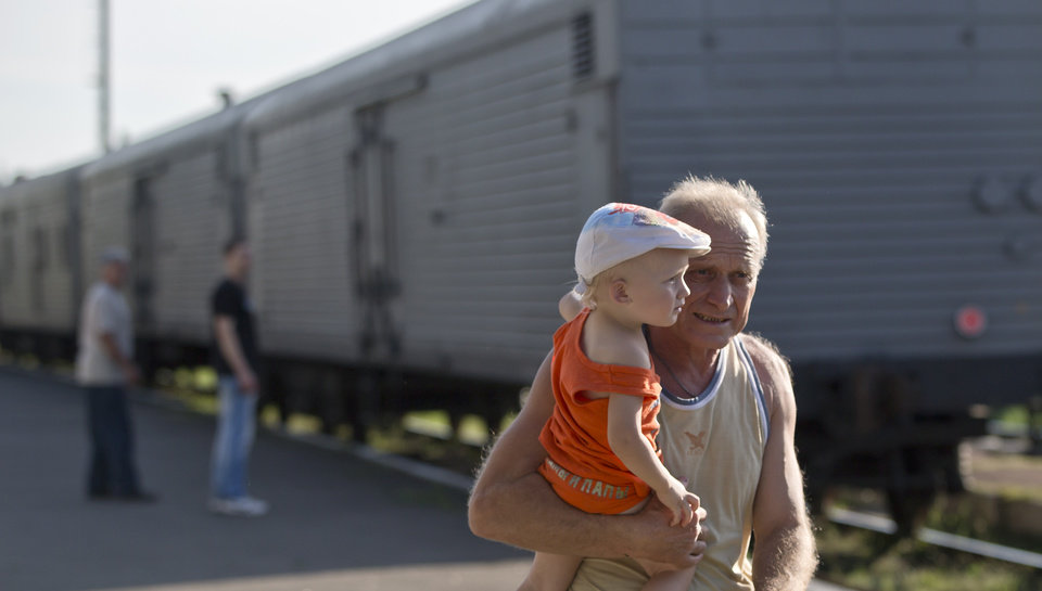 Photo - A man holds a baby as he walks next to a refrigerated train loaded with the bodies of victims, in Torez, eastern Ukraine, 15 kilometers (9 miles) from  the crash site of Malaysia Airlines Flight 17, Sunday, July 20, 2014. Armed rebels forced emergency workers to hand over all 196 bodies recovered from the Malaysia Airlines crash site and had them loaded Sunday onto refrigerated train cars bound for a rebel-held city, Ukrainian officials and monitors said.(AP Photo/Vadim Ghirda)