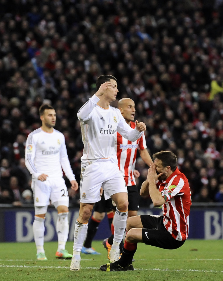 Photo - Real Madrid's Cristiano Ronaldo of Portugal, center, gestures after  a foul against Athletic Bilbao's Carlos Gurpegi, right, during their Spanish League soccer match against Athletic Bilbao, at San Mames stadium in Bilbao, Spain, Sunday, Feb. 2, 2014.  (AP Photo/Alvaro Barrientos)