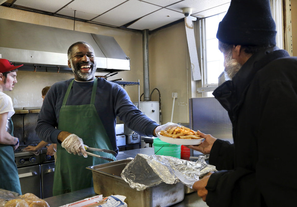 Photo - Richard Hicks, a cafeteria worker at the Jesus House, offers hearty laughter  with the plate of food he serves to Gary Duncan, a homeless man who stepped inside the shelter to warm himself and to gets a hot meal and a cup of coffee as he 