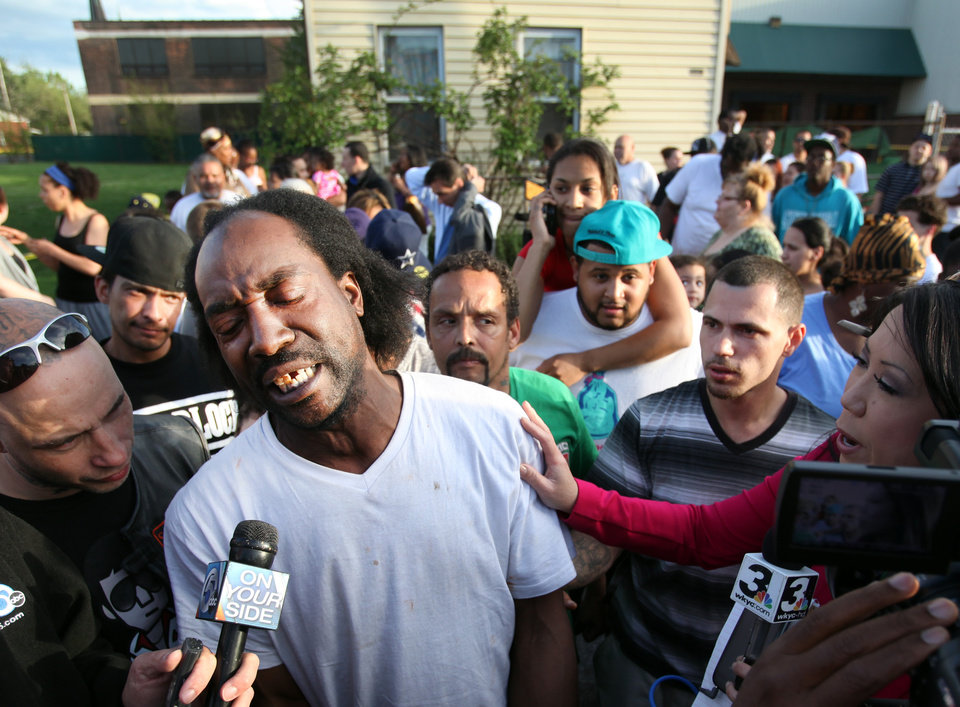 Photo - Neighbor Charles Ramsey speaks to media near the home on the 2200 block of Seymour Avenue, where three missing women were rescued in Cleveland, on Monday, May 6, 2013. Cheering crowds gathered on the street where police said Amanda Berry, Gina DeJesus and Michele Knight, who went missing about a decade ago and were found earlier in the day. (AP Photo/The Plain Dealer, Scott Shaw) MANDATORY CREDIT CLEVELAND PLAIN DEALER