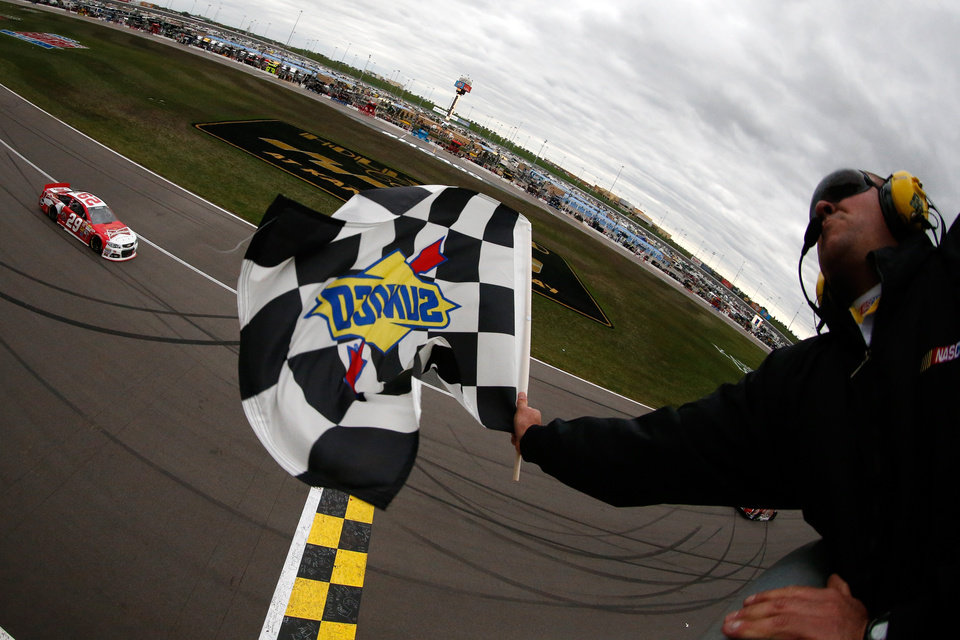 Photo - Driver Kevin Harvick (29) takes the checkered flag to win a NASCAR Sprint Cup series auto race at Kansas Speedway in Kansas City, Kan. (AP Photo/Chris Graythen, Pool)