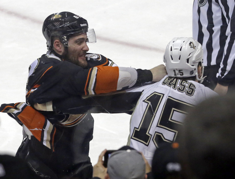 Photo - Anaheim Ducks left winger Patrick Maroon (62) and Pittsburgh Penguins left winger Tanner Glass (15) fight, drawing each a five-minute penalty, in the first period of an NHL hockey game in Anaheim, Calif., Friday, March 7, 2014.  (AP Photo/Reed Saxon)