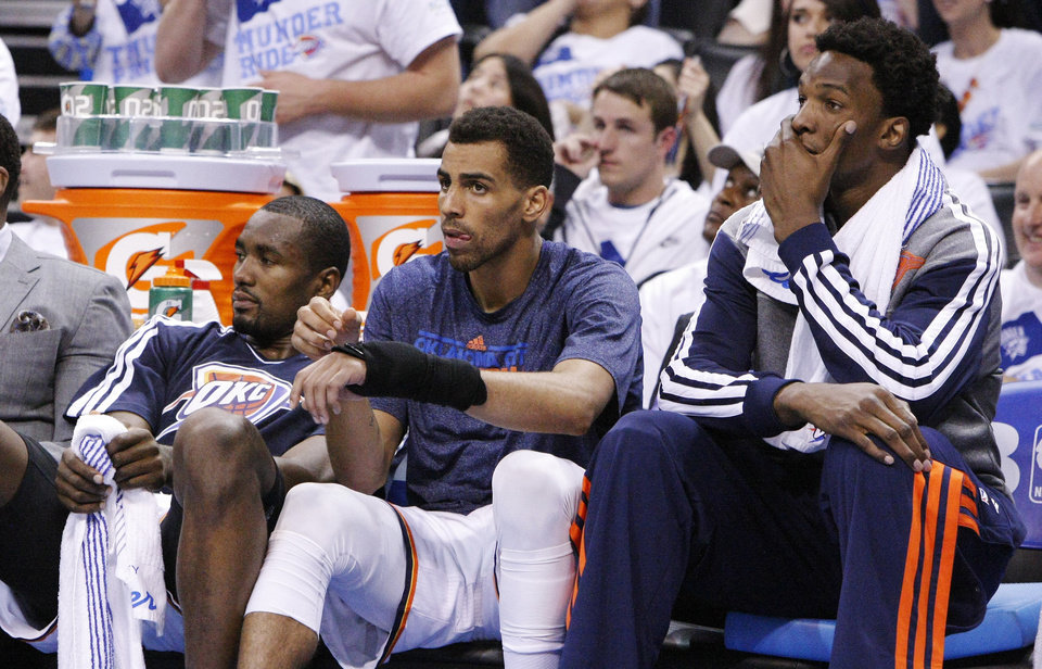 Oklahoma City Thunder forward Serge Ibaka (9), guard Thabo Sefolosha (2) and center Hasheem Thabeet (34) watch from the bench during the second half of Game 5 of their Western Conference Semifinals NBA basketball playoff series against the Memphis Grizzlies in Oklahoma City, Wednesday, May 15, 2013. Memphis won 88-84. (AP Photo/Alonzo Adams)
