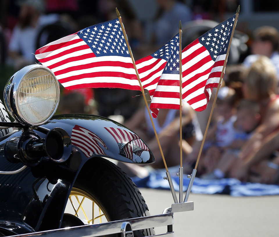Photo - American flags ride on a car during the Edmond LibertyFest Parade in downtown Edmond, Okla., on Independence Day, Friday, July 4, 2014. Photo by Nate Billings, The Oklahoman