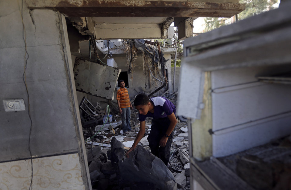 Photo - Palestinians inspect the rubble of a home after it was hit by an Israeli missile strike in Gaza City, early Monday, June 16, 2014. Israel's military said it carried out airstrikes on five weapons and militant sites in Gaza, following overnight rocket fire from the coastal strip into Israel. Two rockets were intercepted and a third fell in an open area in Israel, causing no injuries, the military said. (AP Photo/Hatem Moussa)